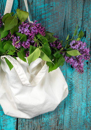 lilacs in muslin cotton sack on rustic turquoise painted wood