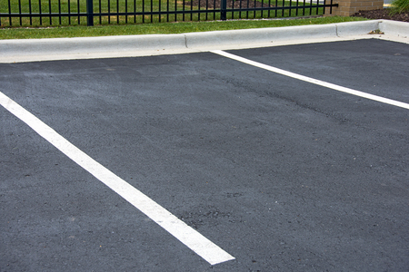 Empty parking space with white lines and curb