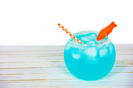 turquoise cocktail drink in fishbowl with orange candy goldfish and checkered straw