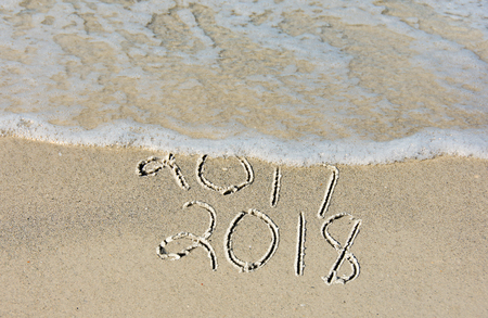erased: New Year 2018 text in beach sand with frothy ocean surf