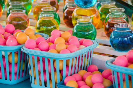 colorful balls and water in bowls for carnival game