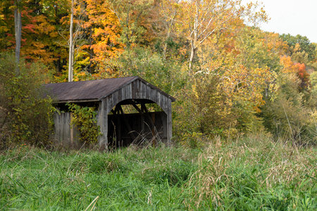 old covered wooden bridge in autumn foliage Stock Photo