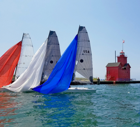 spinnaker: Red white and blue spinnakers on sailboats in Holland Michigan harbor with lighthouse