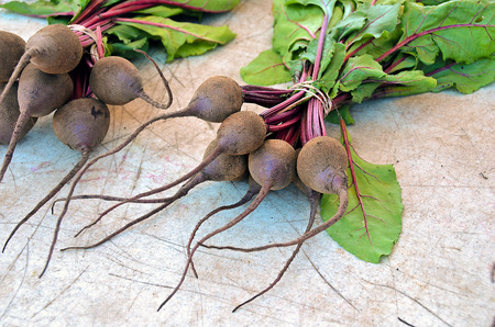 Raw beets bunch on textured weathered wood