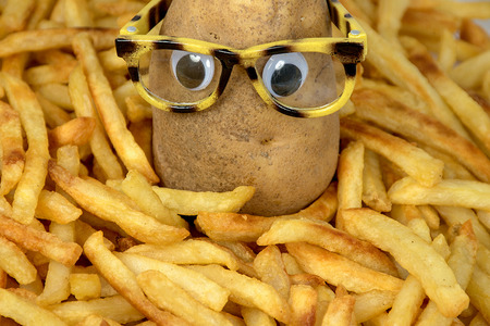 potato with eyeglasses in pile of golden french fries