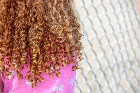 little girl with red curly hair standing by chain link fence
