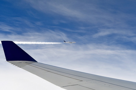 pair of jet airplanes in blue sky with vapor contrail