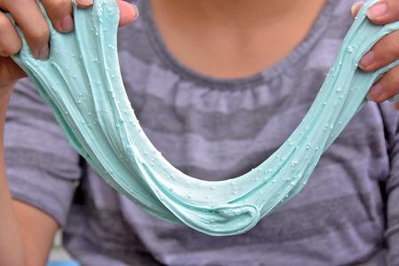 young girl stretch aqua colored slime Standard-Bild