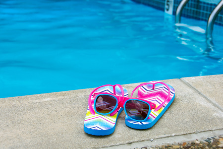 sunglasses on flip-flops by swimming pool edge