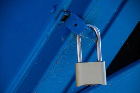 security padlock on blue metal latch