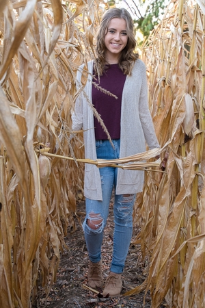 smiling teenage girl with frayed blue jeans in autumn cornfield