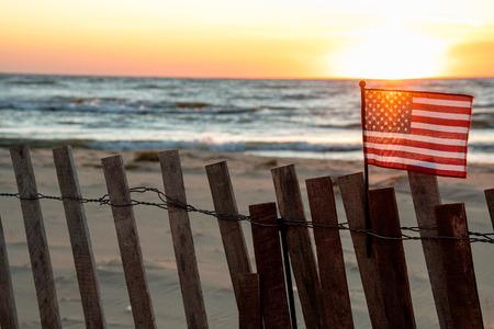 sunset illuminating American flag on beach fence
