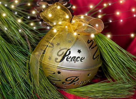 gold Christmas ornament on pine with word peace and light string