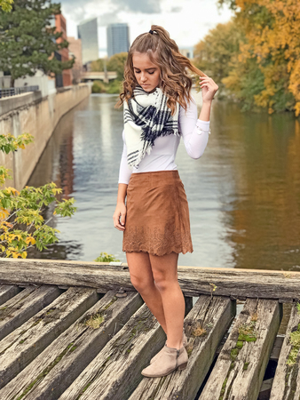 Caucasian teenage girl in short skirt on wooden bridge with city and river background