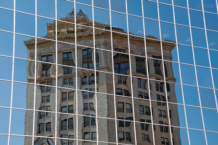 old ornate building reflection in new glass city skyscraper
