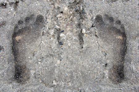 pair of footprints in grungy textured cement Фото со стока