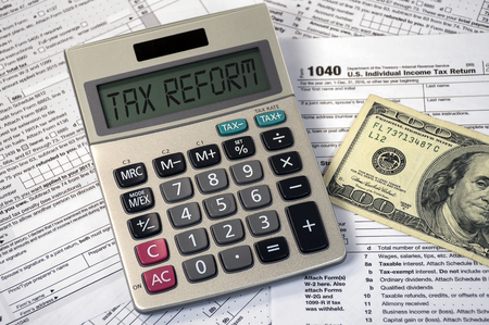 Tax reform text on calculator screen with hundred dollar bill on income tax form