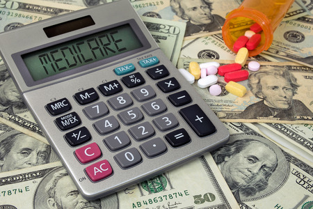Medicare text sign on calculator screen with prescription drugs and pill bottle on American money Stock fotó - 90789217
