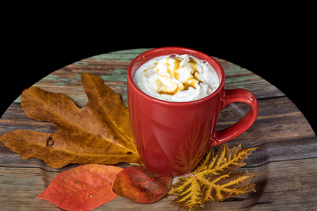 coffee with whipped cream and caramel drizzle in red mug with autumn leaves and wooden plate Imagens