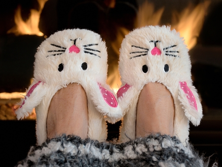 pair of bunny slippers by fireplace with striped afghan