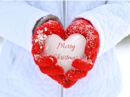 girl wearing red snow covered gloves holding ice heart with Merry Christmas greeting