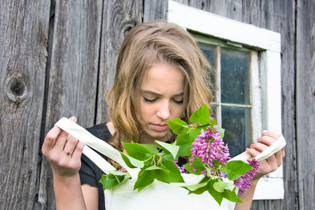 Caucasian teenage girl looking at lilac bouquet in white cloth bag Stock Photo