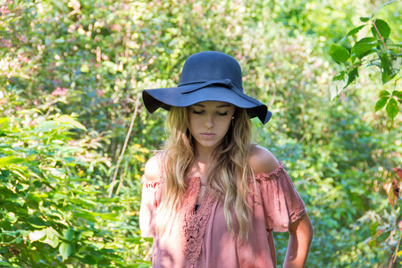 Caucasian teenage girl in sunlit summer woods with serious expression wearing black hat and off the shoulder blouse Stock Photo