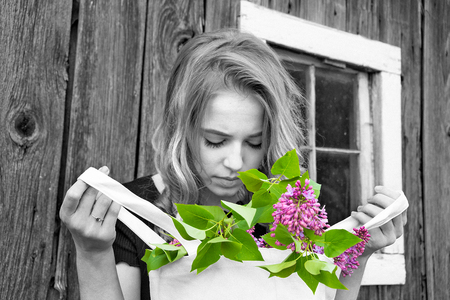 Caucasian teenage girl holding a bag of spring lilac blossoms by rustic barn in selective color effect