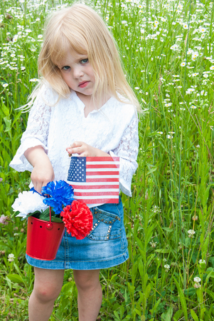frowning little blond girl with carnation bouquet and American flag in red pail in wild daisy field