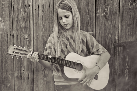 young girl playing guitar by old rustic wooden barn in fog and sepia tones Stock Photo