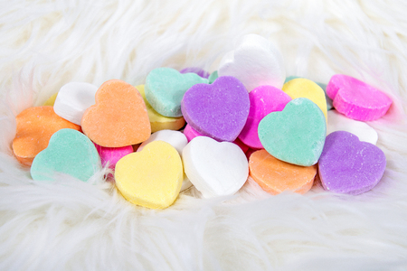 closeup of colorful candy hearts on white fur for Valentines Day