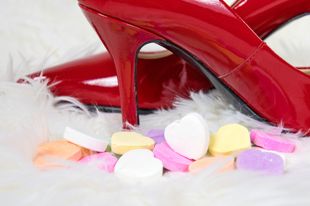 red high heel shoes with Valentine heart candy on white fur