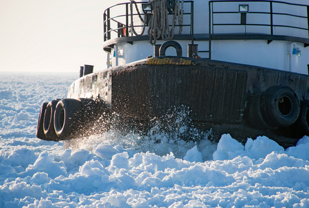 closeup of tugboat hull cutting through thick ice in Lake Michigan Stock Photo