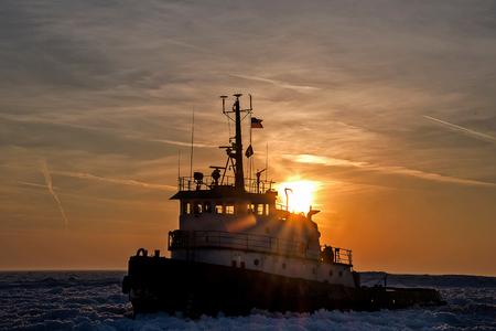Tugboat in Lake Michigan ice at sunset
