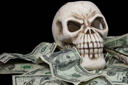human skull in a pile of American currency on black background Stock Photo