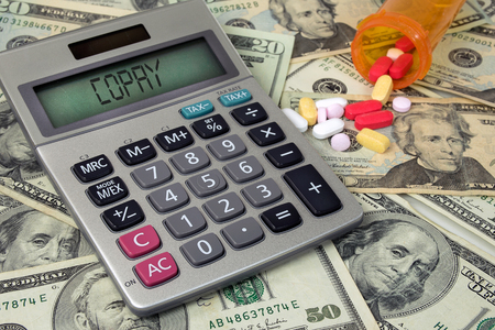 copay text on calculator with money and prescription pills in bottle