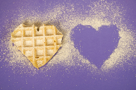 waffle heart sprinkled with powdered sugar on purple background