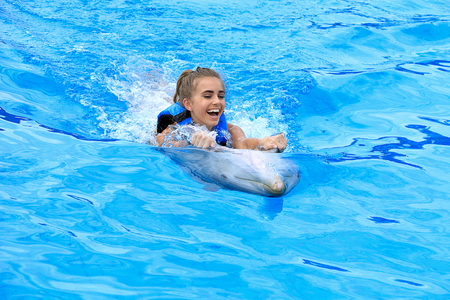 Caucasian teenage girl with dolphin in swimming pool
