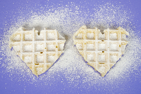 pair of waffle hearts sprinkled with confectioners sugar on purple background