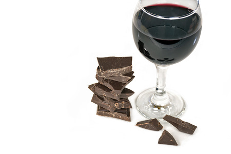 glass of red wine and dark chocolate stack isolated on white background