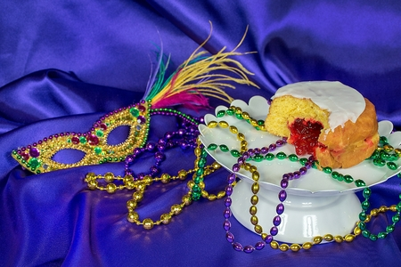 Fat Tuesday paczki with Mardi Gras party beads on white pedestal plate with sequin mask on purple satin Stock Photo