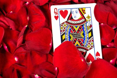 Close up of queen of hearts card in red rose petals