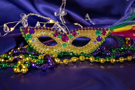 Mardi Gras party beads with gold sequin masquerade mask on purple satin fabric