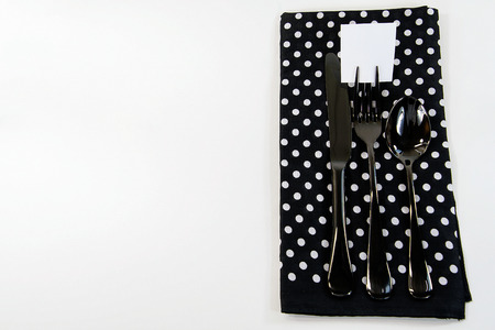 black silverware with blank square paper on fork tine and polka dot napkin on white background Stock Photo