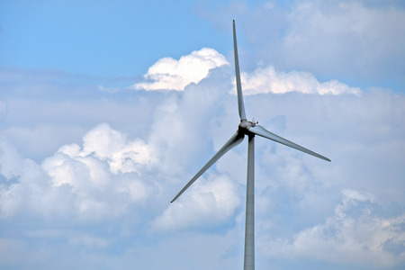 Wind turbine with blue sky and fluffy clouds background