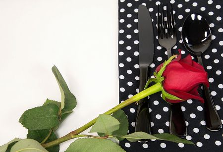 red rose on black silverware and polka dot napkin
