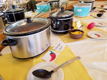 row of crock pots in chili cook off competition in restaurant