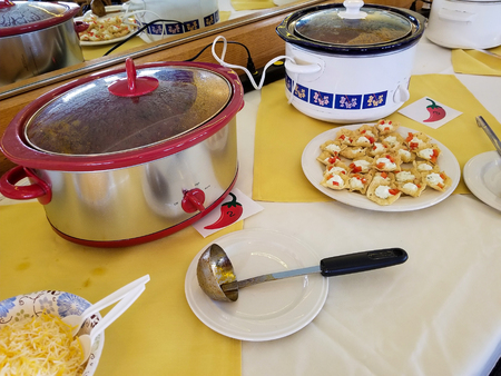 row of crock pots in chili cook off contest with shredded cheese and appetizer plate on tablecloth Stock Photo