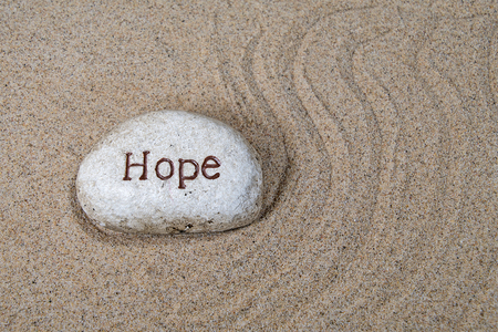 hope text engraved on a rock in beach sand