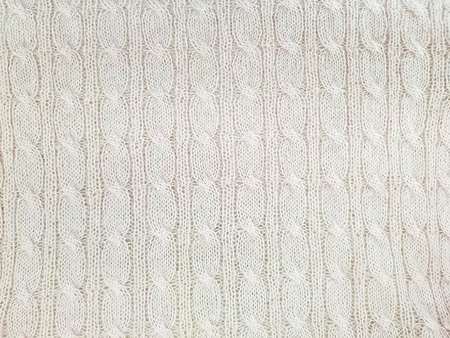 close up of cream colored cable knit pattern background